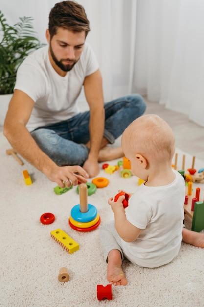 Hoge hoek van vader spelen met baby thuis Gratis Foto