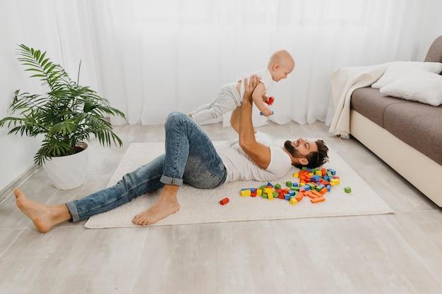 Hoge hoek van vader spelen op de vloer met baby Gratis Foto