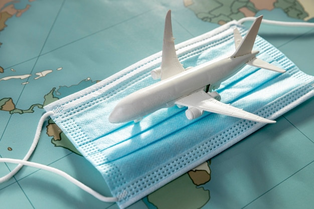 Hoge hoek van vliegtuigbeeldje op medisch masker Gratis Foto