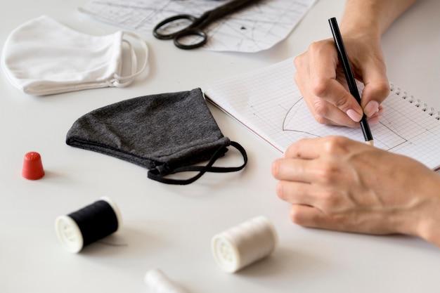 Hoge hoek van vrouw die te naaien gezichtsmasker ontwerpt Premium Foto