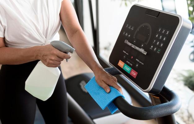 Hoge hoek van vrouw fitnessapparatuur schoonmaken Gratis Foto