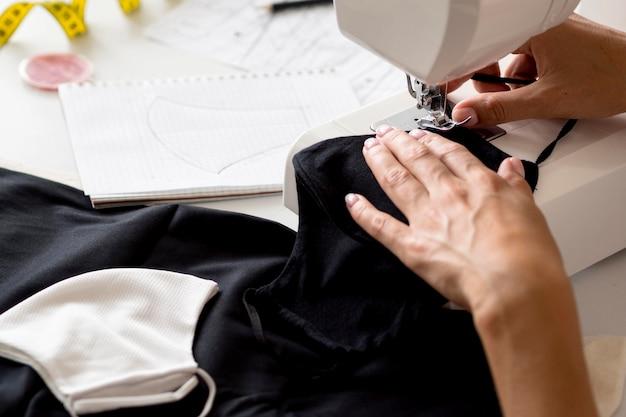 Hoge hoek van vrouw naaien gezichtsmasker uit textiel Gratis Foto