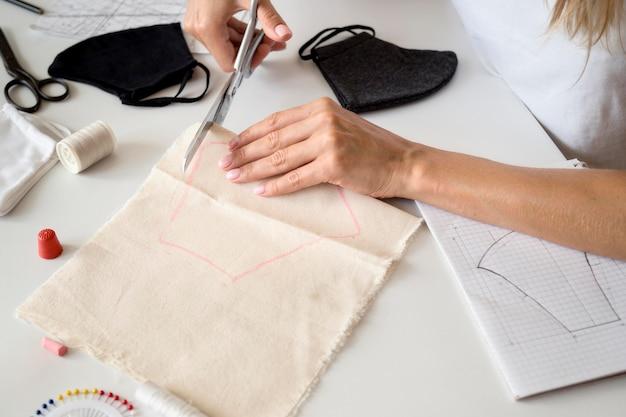 Hoge hoek van vrouw snijden textiel om gezichtsmasker te naaien Gratis Foto
