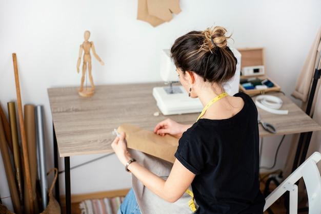 Hoge hoek van vrouwelijke kleermaker die in de studio werkt Gratis Foto