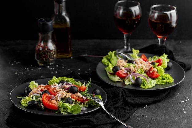 Hoge hoek verse maaltijd met donker servies en wijnglazen Gratis Foto