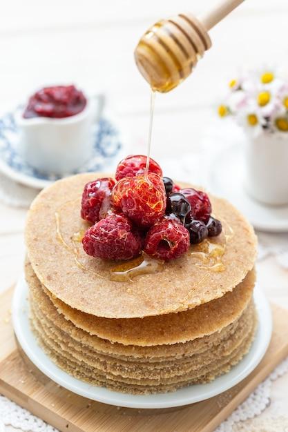 Hoge hoek verticale close-up shot van rauwe veganistische pannenkoeken met honing en bessen Gratis Foto