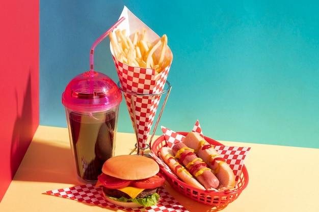 Hoge hoek voedselregeling met sapkop en cheeseburger Gratis Foto