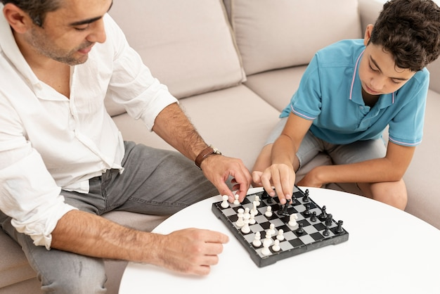 Hoge hoek volwassene en kind schaken Gratis Foto