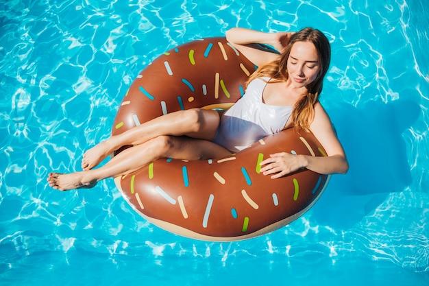 Hoge hoek vrouw poseren en glimlachend in donut zwemmen ring Gratis Foto