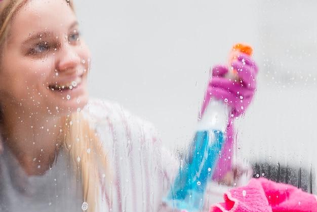 Hoge hoek vrouw schoonmaak ramen Gratis Foto