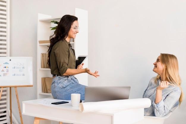 Hoge hoek vrouwtjes op kantoor praten Gratis Foto