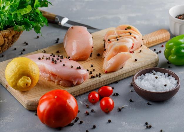 Hoge hoek weergave kippenborsten op snijplank met citroen, tomaten, zout op grijze ondergrond Gratis Foto