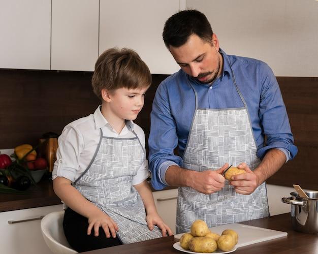 Hoge hoek zoon en vader aardappelen schoonmaken Gratis Foto