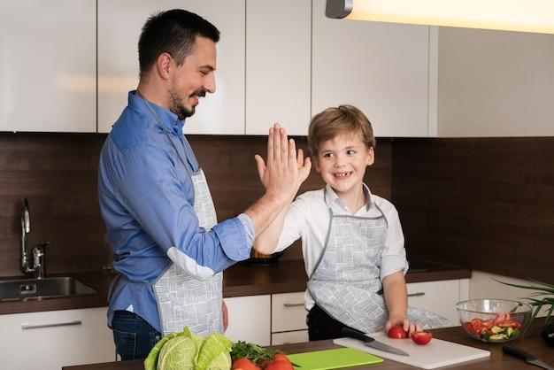 Hoge hoek zoon en vader high five Gratis Foto