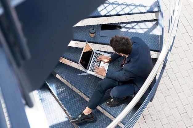 Hoge hoekadvocaat met laptop, tablet en koffie Gratis Foto
