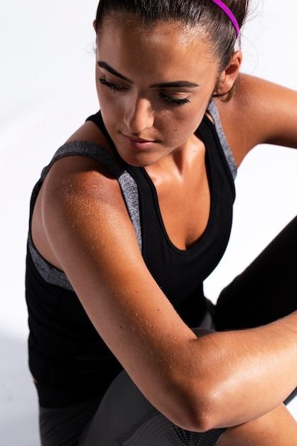 Hoge hoekatleet die in gymnastiekkostuum neer kijkt Gratis Foto