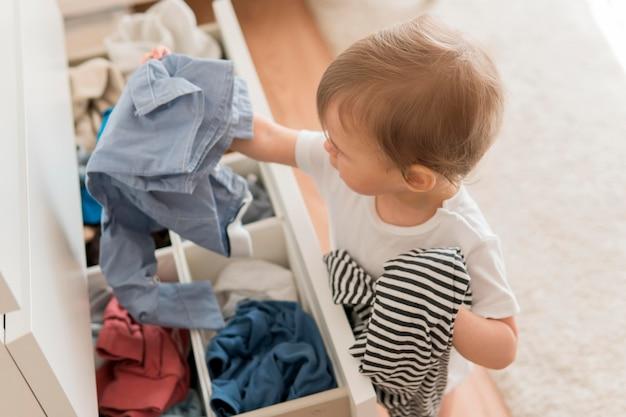 Hoge hoekbaby die kleren van lade neemt Gratis Foto
