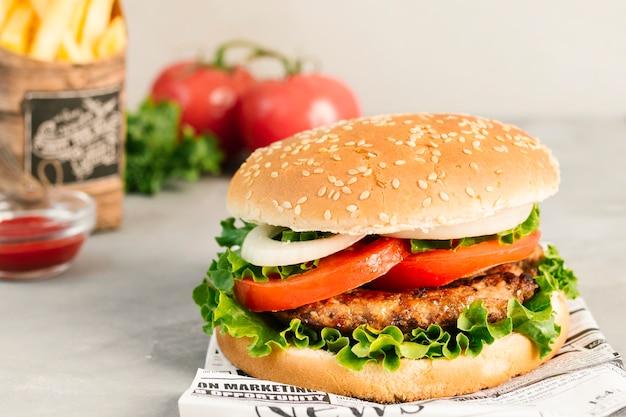 Hoge hoekclose-up van hamburger en gebraden gerechten op krant Gratis Foto