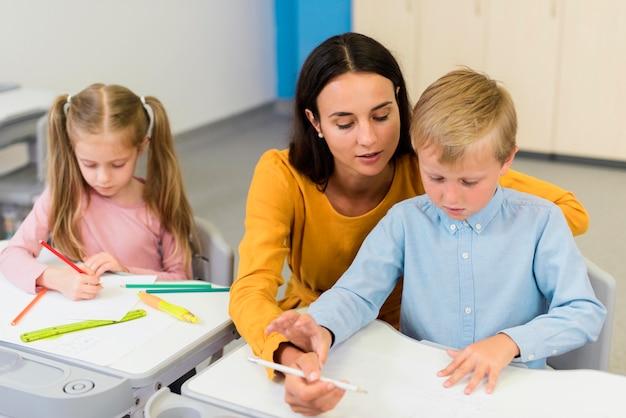 Hoge hoekleraar helpt een kleine jongen in de klas Premium Foto