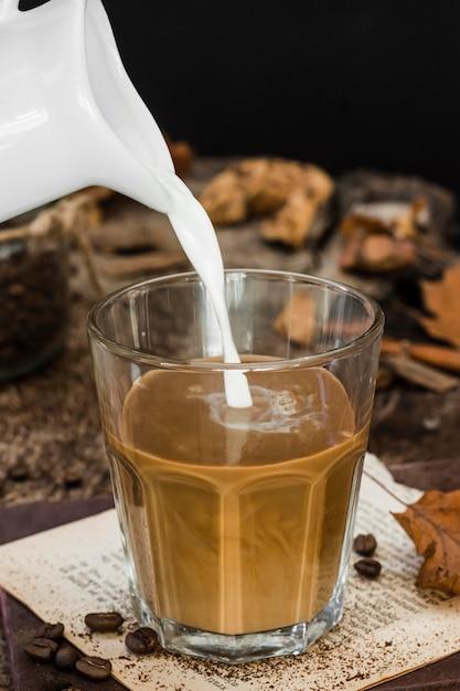 Hoge hoekmelk die in glas met koffie wordt gegoten Premium Foto
