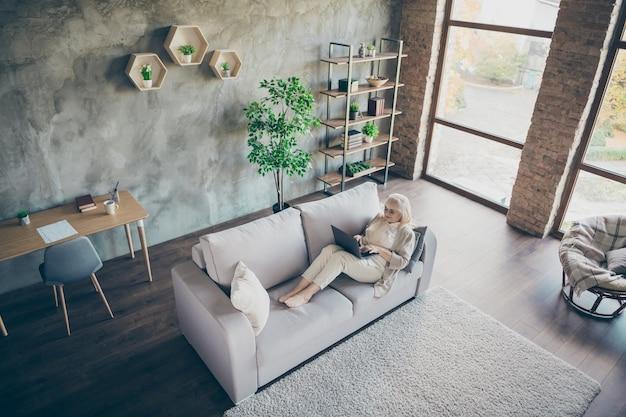 Hoge hoekmening foto van blonde leeftijd oma met behulp van laptop lezen kleinkinderen e-mail typen antwoord liggend sofa divan woonkamer ruime appartementen binnenshuis Premium Foto
