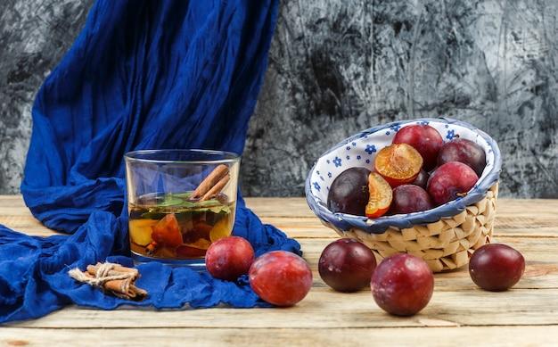 Hoge hoekmening gefermenteerde drank en kaneel op blauwe sjaal met een kom pruimen op houten bord en donkergrijs marmeren oppervlak. horizontaal Gratis Foto