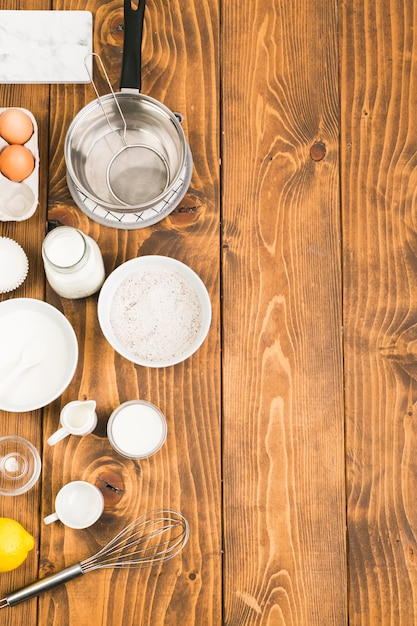 Hoge hoekmening van bakken gebruiksvoorwerpen en ingrediënten voor het voorbereiden van cookies gerangschikt op houten tafel Gratis Foto