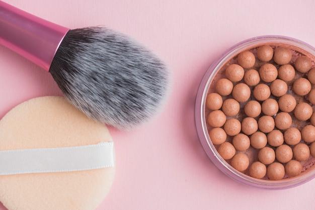 Hoge hoekmening van bronzing parels; spons en make-upborstel op roze oppervlakte Gratis Foto