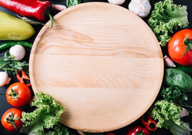 Hoge hoekmening van cirkelvormige houten plaat omringd met verse groenten Gratis Foto