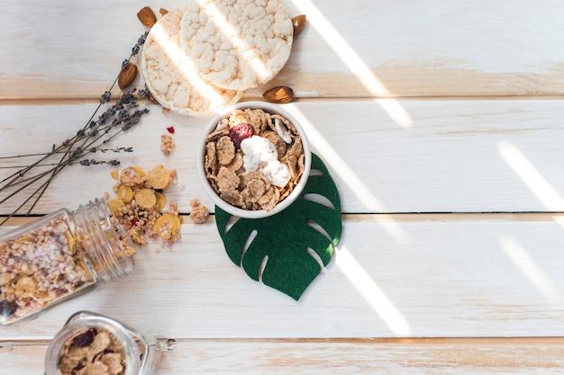 Hoge hoekmening van cornflakes in kom in de buurt van gemorste granola en rijstcrackers op houten oppervlak Gratis Foto