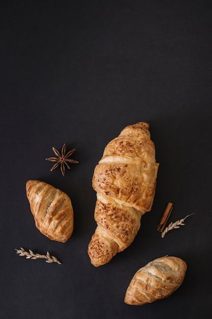 Hoge hoekmening van croissants; specerijen en granen op zwarte achtergrond Gratis Foto
