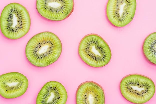 Hoge hoekmening van de plakken van het kiwifruit op roze achtergrond Gratis Foto