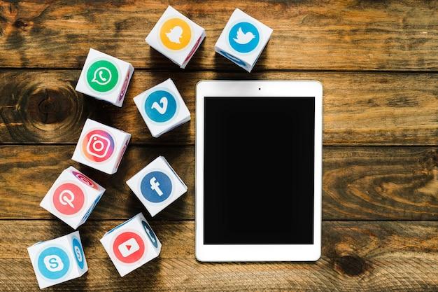 Hoge hoekmening van digitale tablet in de buurt van vakken met media iconen Gratis Foto