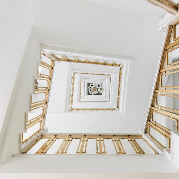 Hoge hoekmening van een moderne wenteltrap in een tentoonstelling onder de lichten Gratis Foto