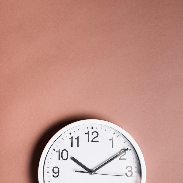 Hoge hoekmening van een wekker op bruine achtergrond Gratis Foto