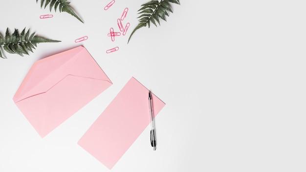 Hoge hoekmening van envelop; pen; kunstmatige varens en paperclips op witte achtergrond Gratis Foto