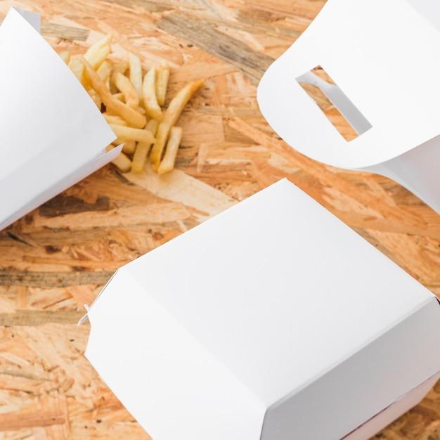 Hoge hoekmening van frieten en voedselpakketspot omhoog op houten bureau Gratis Foto