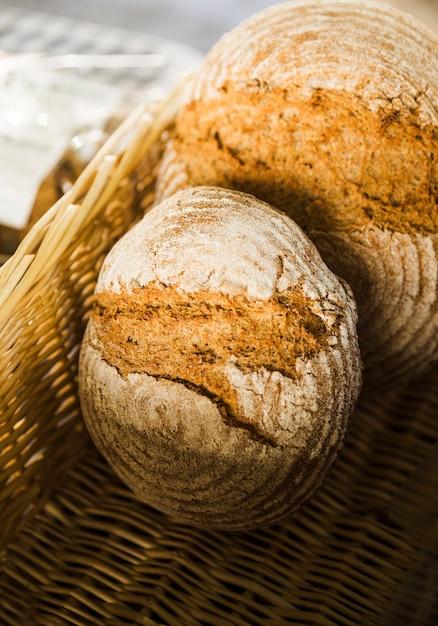 Hoge hoekmening van gebakken brood in rieten mand bij bakkerijkraam Gratis Foto