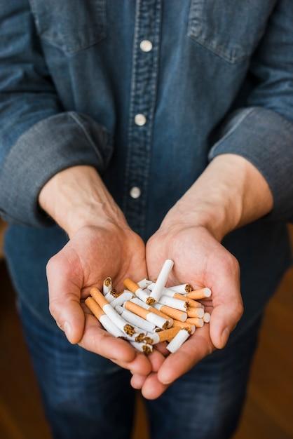 Hoge hoekmening van gebroken sigaretten in man hand Gratis Foto