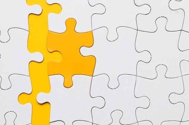 Hoge hoekmening van gele puzzel stuk gerangschikt met witte stukken Gratis Foto