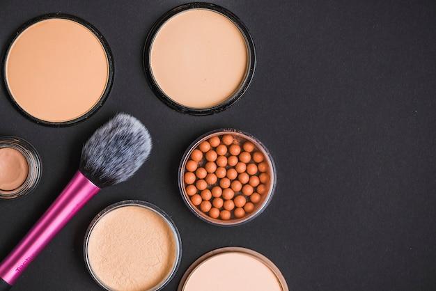 Hoge hoekmening van gezichtspoeder; bronzing parels en make-up borstel op zwarte achtergrond Gratis Foto