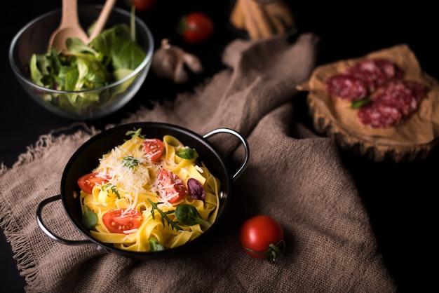 Hoge hoekmening van gezonde pasta in kookpot op jute textiel met cherry tomaat en salade Gratis Foto