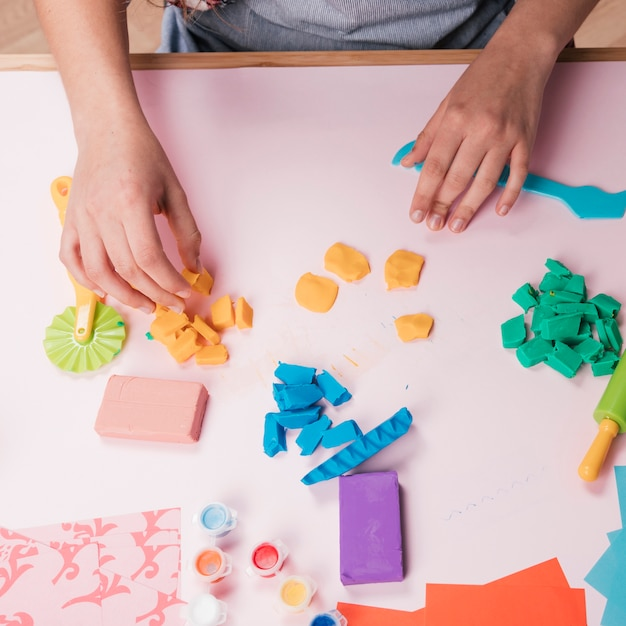 Hoge hoekmening van hand met kleurrijke klei Gratis Foto