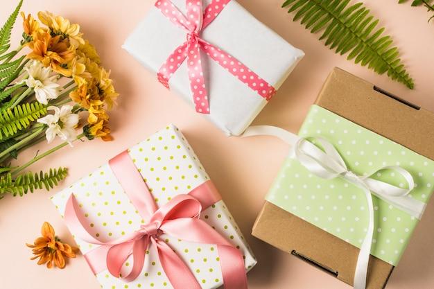 Hoge hoekmening van huidige dozen en bloemboeket met bladeren Gratis Foto