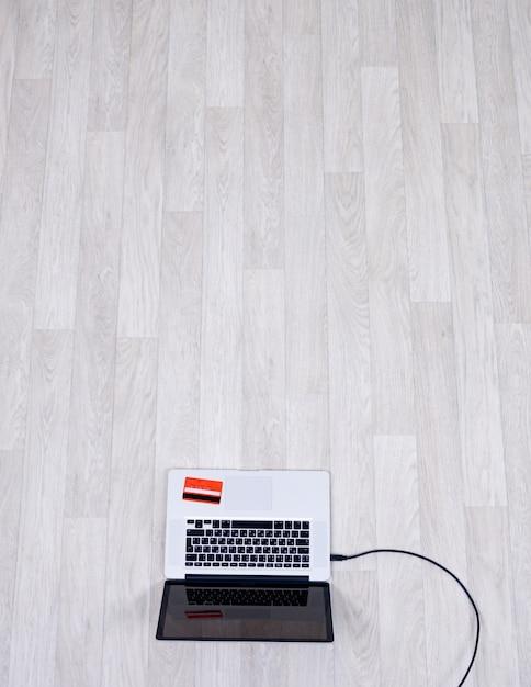Hoge hoekmening van laptop is op de vloer in lege kamer met creditcard erop Gratis Foto