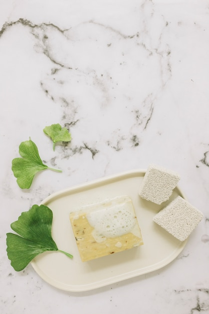 Hoge hoekmening van puimsteen; zeep en gingkoblad op marmeren achtergrond Gratis Foto