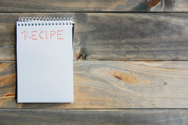 Hoge hoekmening van receptwoord op spiraalvormige blocnote over houten achtergrond Gratis Foto