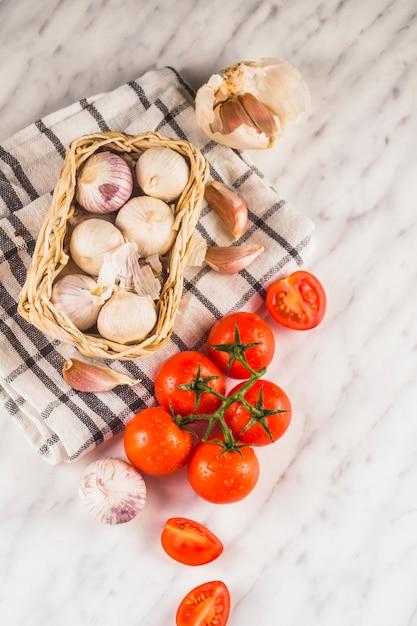 Hoge hoekmening van rode tomaten; uien; knoflookteentjes en doek op marmeren oppervlak Gratis Foto