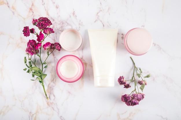 Hoge hoekmening van schoonheid crèmes en bloemen op marmer Gratis Foto