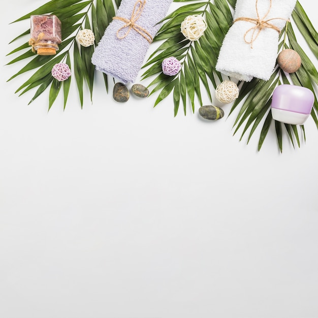 Hoge hoekmening van spa stenen; handdoeken; hydraterende creme; scrub fles en bladeren op witte achtergrond Gratis Foto